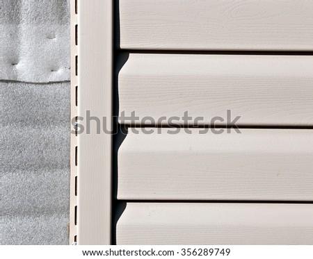 Installation on facade of the house panels beige vinyl siding - stock photo