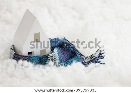 installation with winter background with a house wrapped in warm scarf - stock photo