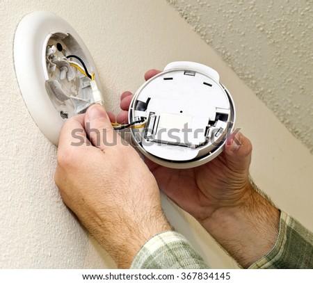 Installing a new smoke alarm in home/ Installing New Smoke Alarm - stock photo