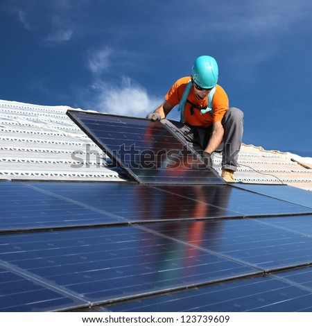 installing alternative energy photovoltaic solar panels on roof - stock photo