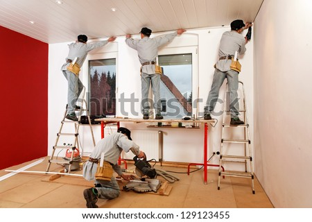 Installing Crown Molding on Living Room Ceiling. - stock photo