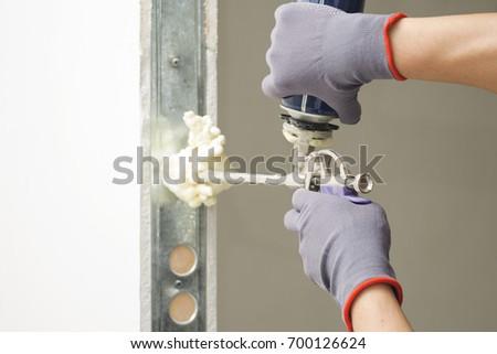Installing Door Unit. Workman Fixing The Door Frame Using A Mounting Foam