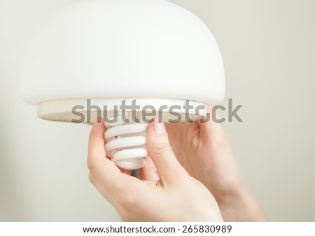 Installing energy efficient compact fluorescent light - stock photo