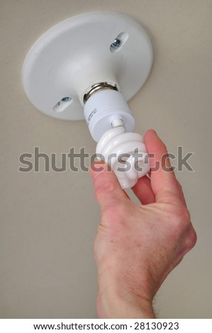 Installing energy efficient compact fluorescent light (CFL) - stock photo