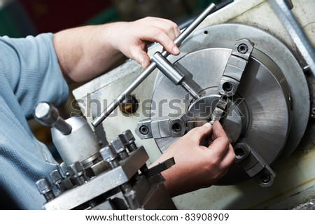 installing equipment with metal detail for operation on turning lathe machine with cutting tool - stock photo