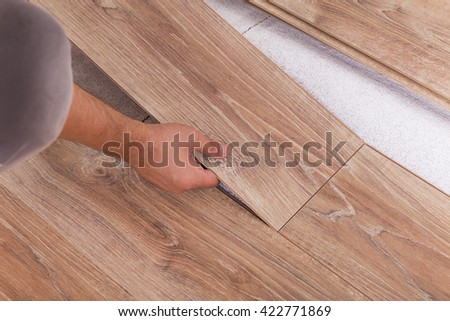 Installing laminate flooring. Carpenter lining parquet boards to each other fitting a plank - stock photo