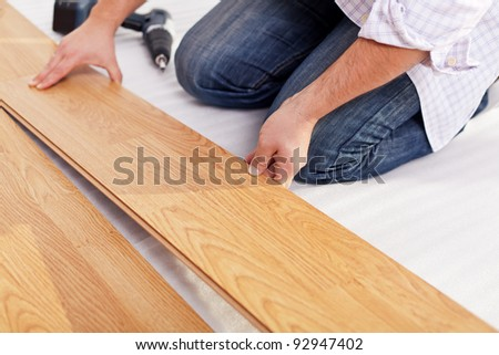 Installing laminate flooring fitting the next piece - focus on hand - stock photo