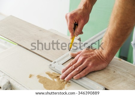 Installing laminate flooring. Worker measures off a piece of board to cut. - stock photo