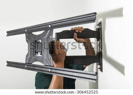 Installing mount TV on the wall at home - stock photo