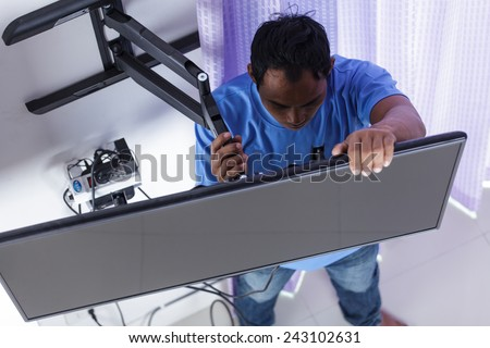 Installing mount TV on the wall at home or office - stock photo