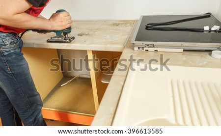 Installing new induction hob in modern kitchen - stock photo