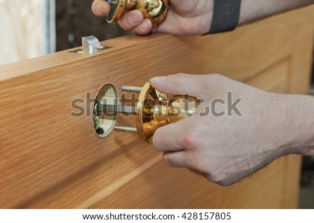 Installing new interior door,  close-up carpenter hand  holding spherical shaped brass door handle knob. - stock photo