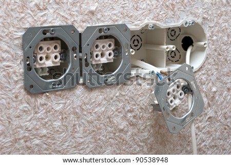 Installing outlet and electrical box in a construction - stock photo