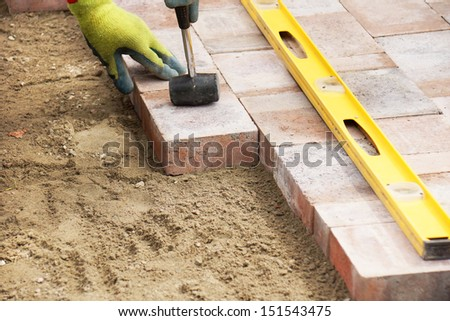 Installing paver bricks on patio, mallet to level the stones - stock photo