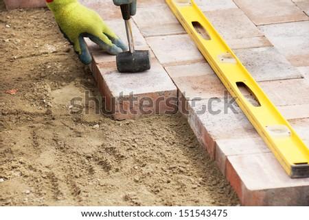 Installing paver bricks on patio, mallet to level the stones - stock photo