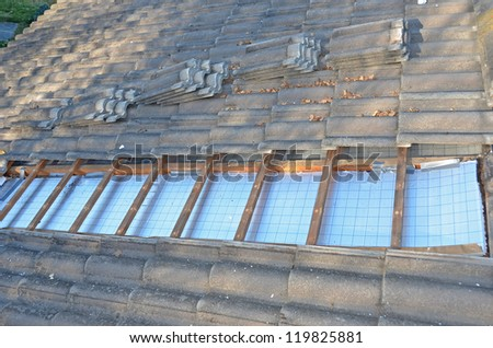 Installing roof insulation in a home to reduce heat wastage and heating bills, and help reduce global warming - stock photo