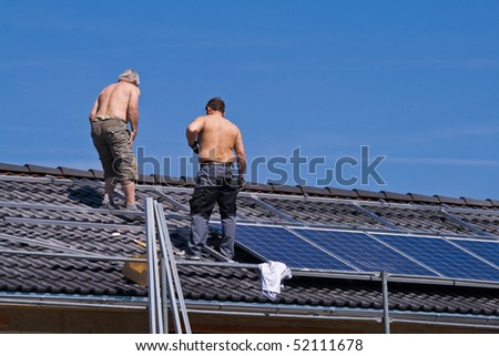 Installing solar modules on a roof - stock photo