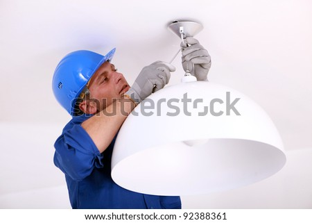 Installing the ceiling light. - stock photo