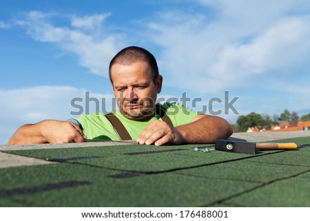 Installing the last strip of bitumen roof shingles - worker measuring with tape measure - stock photo
