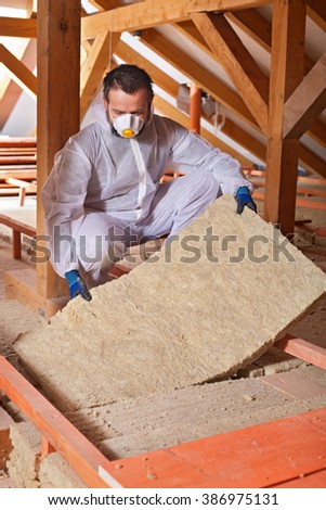 Installing thermal insulation layer on a house - worker fitting mineral wool panel into place, copyspace - stock photo