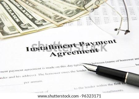 installment payment agreement document with glasses and filler - stock photo