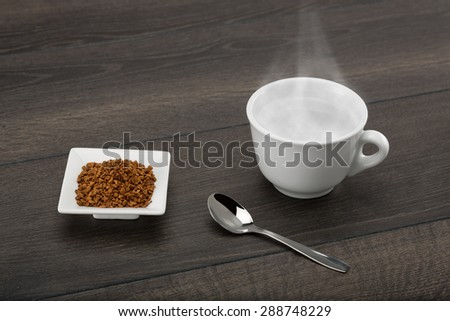 Instant coffee granules ready for the hot water. On dark wooden table. - stock photo