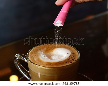 Instant crystal sugar dissolves in cappuccino coffee - stock photo