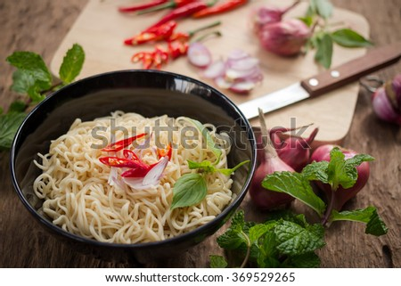 Instant noodles in Ceramic cop and vegetable side dishes on wood background - stock photo