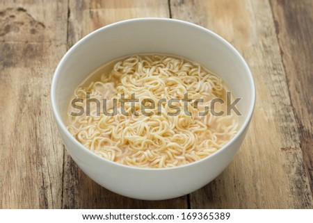Instant noodles in white dish on wood background - stock photo