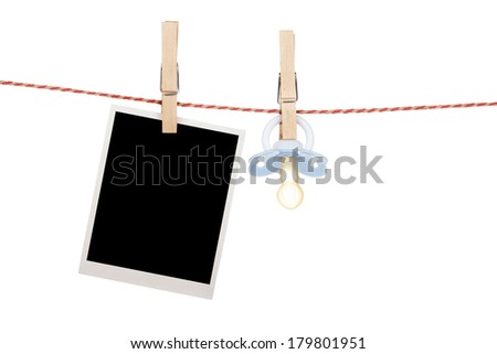 Instant photo and pacifier hanging on the clothesline. Isolated on white background