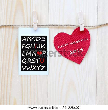 Instant photo and red fabric heart hanging on the clothesline, wooden background, valentine template - stock photo