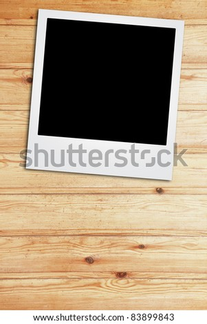 instant photo frame on wooden background