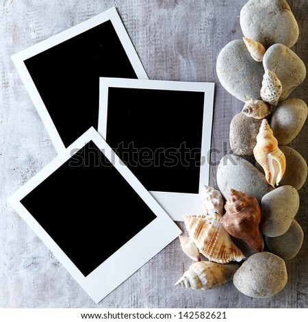 Instant photo frames on the wooden background with seashells around - stock photo