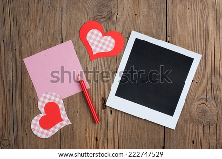 Instant photo with blank note, pencil and paper hearts on old wooden background - stock photo