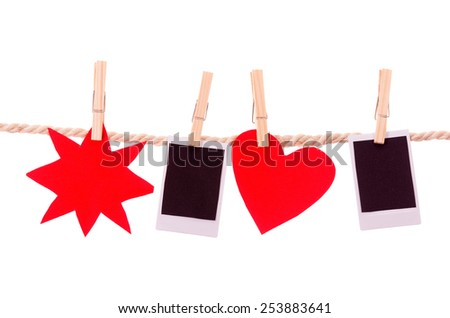 instant photographs and red shapes hanging on a rope clothesline isolated on white - stock photo