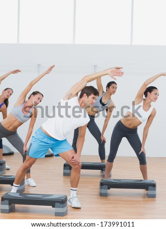 Instructor and fitness class doing stretching exercise in fitness studio