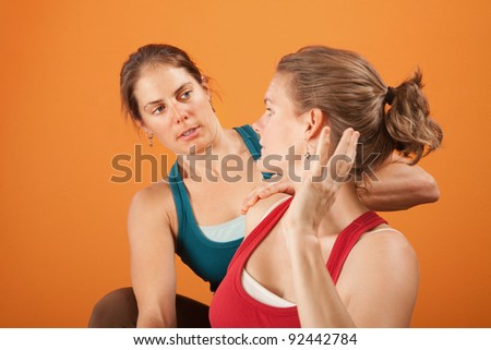 Instructor and student in yoga workout clothes - stock photo
