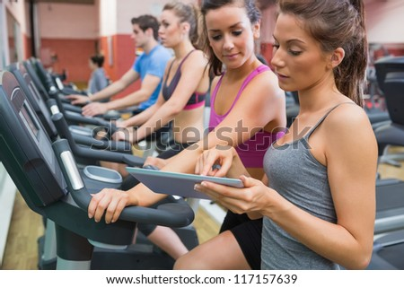 Instructor and woman in the gym on the exercise bicycle