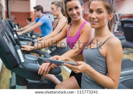 Instructor and woman smiling in the gym on the exercise bicycle