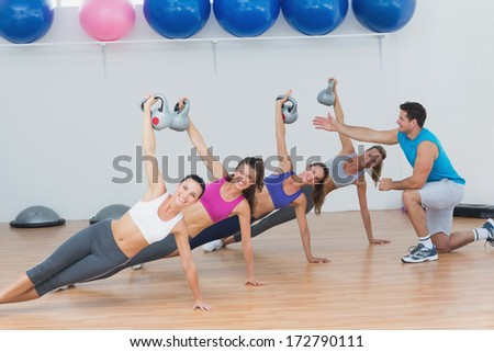 Instructor assisting fitness class with kettlebells in the gym - stock photo