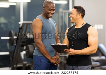 instructor explaining membership form to client in health club - stock photo