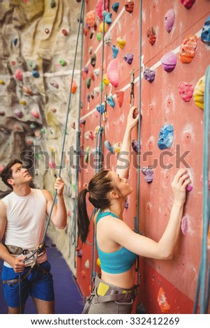 Instructor guiding woman on rock climbing wall at the gym - stock photo