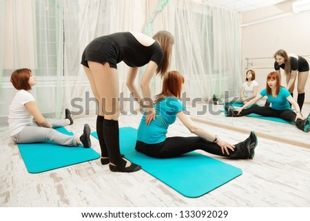 Instructor helping redhead caucasian woman at fitness exercise