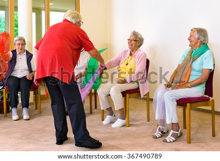 Instructor helping smiling women use colorful scarves in simple physical rehabilitation exercises - stock photo
