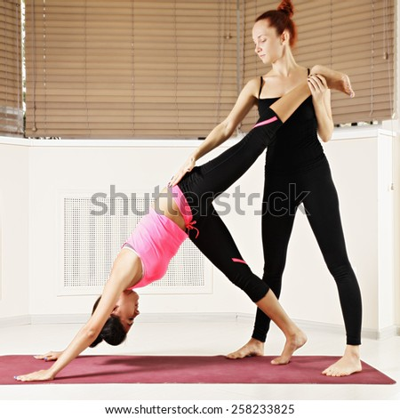 Instructor holding student's leg while assisting in yoga exercise - stock photo