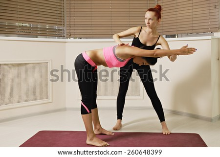 Instructor keeping student's back flat while exercising yoga in gym - stock photo