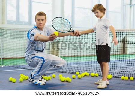 Instructor or coach teaching child how to play tennis on a court indoor - stock photo