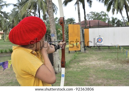 Instructor showing archery demonstration to students in shallow depth of field. - stock photo