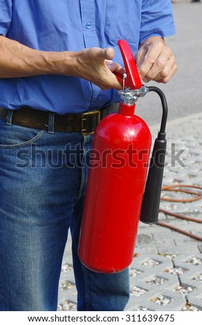 Instructor showing how to use a fire extinguisher on a training fire - stock photo