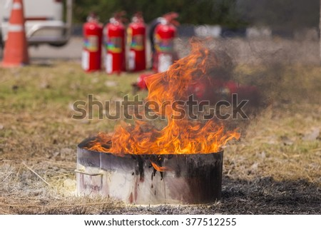 instructor showing how to use a fire extinguisher on a training fire. - stock photo
